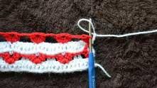 Вводим крючок под последний красный столбик (если получится, то под одну красную ниточку на столбике), захватываем белую петельку и вытягиваем ее.