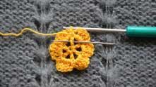 Поворачиваем цветок на изнанку. Под ССН, над которым у нас рабочая петля, связать соединительный столбик.  Вводим крючок так же, как введена иголка, захватываем нить и вытягиваем ее из-под столбика и через петлю на крючке.