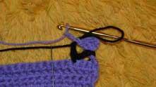 Два столбика на полотне пропускаем, в третий вяжем 1 СБН и набираем 2 в.п. сиреневой ниткой.