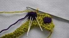 Набрали 1 зеленую воздушную петлю и вытягиваем 4 петли, вводя крючок между фиолетовыми столбиками, как введены иголки.