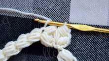 Теперь крючок вводим в петельку, которая получилась, когда мы придерживали ниточку. Захватываем рабочую нить и протягиваем через все петли на крючке, как бы делая соединительную петлю.