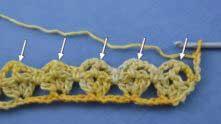 Ряд 3. Вяжем ряд ракушек. Все ракушки вяжем в вершинки столбиков с накидом.