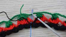 Зеленую нить обрезать и возвращаемся к вязанию черной ниточкой. Петлю вытянули на высоту 1,5-2 см, вяжем пышный столбик из 4-х полустолбиков, вводя крючок в промежуток между двумя пышными столбиками (см. маркер) и захватывая красную и зеленую цепочки так, чтобы они оказались внутри пышного столбика.