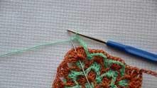 В уголке столбик без накида вяжем между ракушками. Немножко распихайте их, чтобы зеленая ниточка впихнулась покраше между ними.