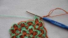 Сцепили зеленую арку с рыжей ракушкой соединительным столбиком и вяжем ряд зеленых ракушек.